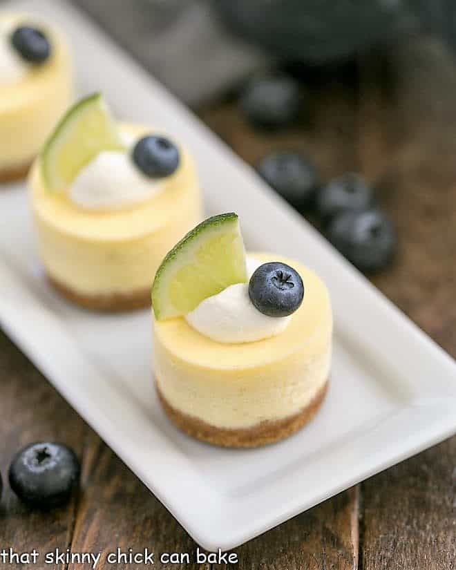 Mini Margarita Cheesecakes topped with cream, a lime slice and a blueberry on a white tray