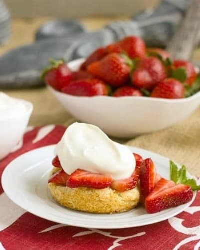 Strawberry Shortcakes with White Chocolate Whipped Cream on a white plate next to a bowl of strawberries
