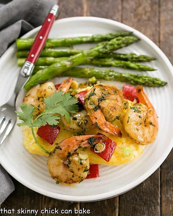 Cheesy Shrimp and Grits Casserole on a white dinner plate with asparagus