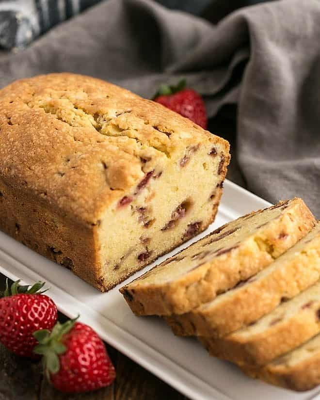 Loaf of Fresh Strawberry Pound Cake on a white ceramic tray with half cut into slices