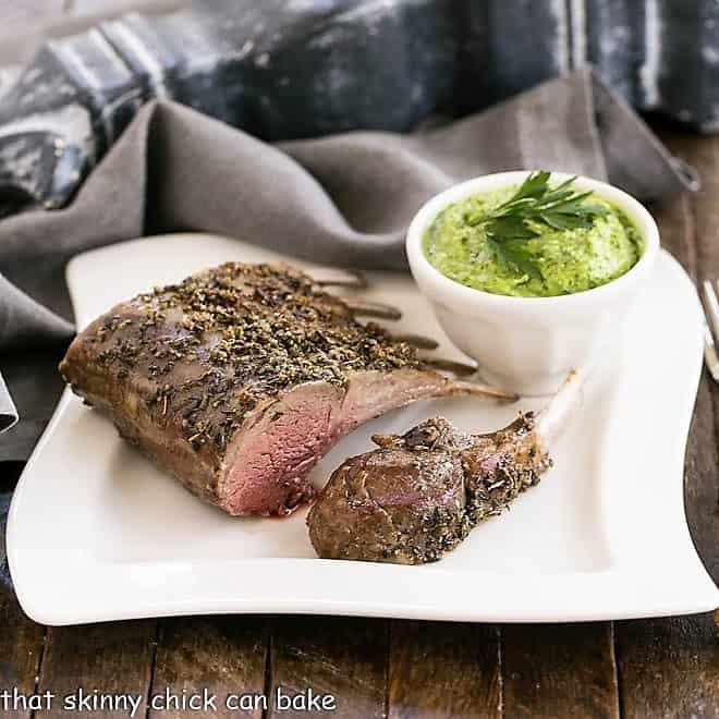 Herb Crusted Rack of Lamb on a white dinner plate with a bowl of parsley pesto