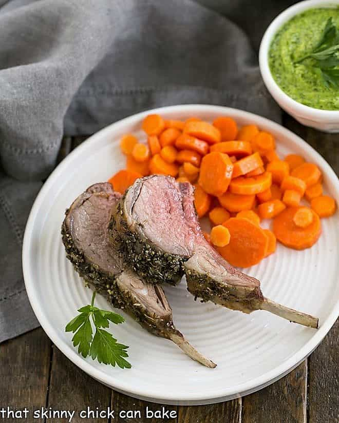 Herb Crusted Rack of Lamb slices on a white plate with carrot coins