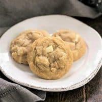 3 white chocolate macadamia nut cookies on a white plate