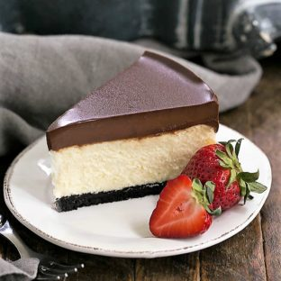 Ganache Topped Cheesecake on a white plate with ripe strawberries to garnish