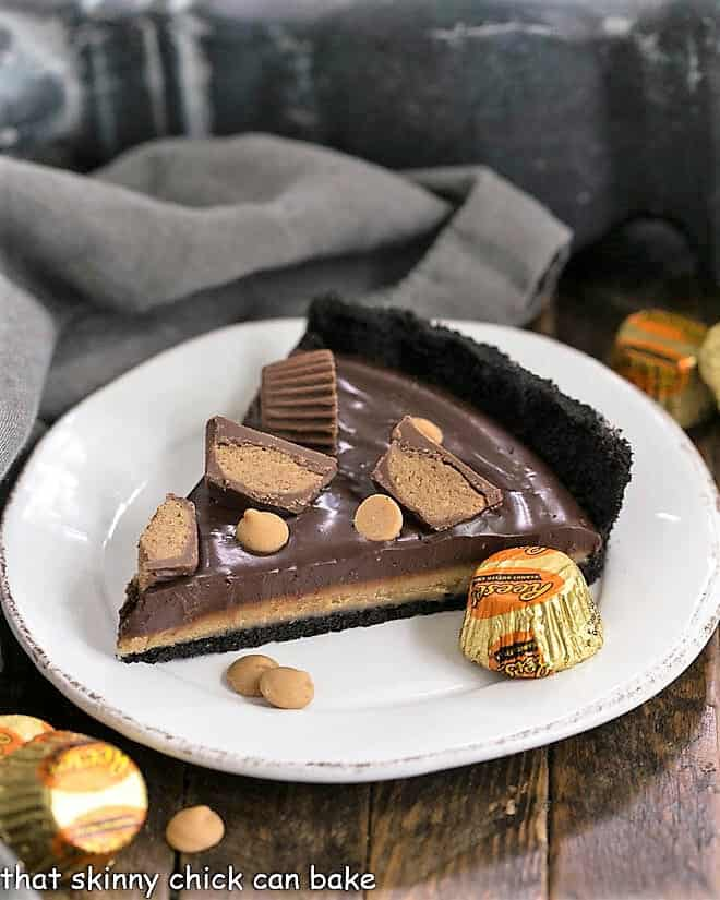 Slice of Reese's Peanut Butter Pie on a white dessert plate with mini Reeses to garnish