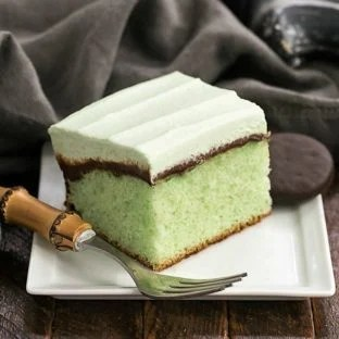A slice of creme de menthe cake on a white plate with a bamboo handle fork