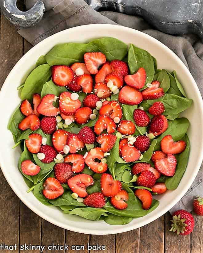 Overhead view of an easy strawberry spinach salad in a white ceramic bowl