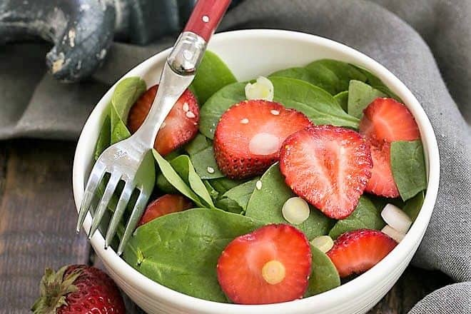 Strawberry spinach salad in a salad bowl with a red handled fork