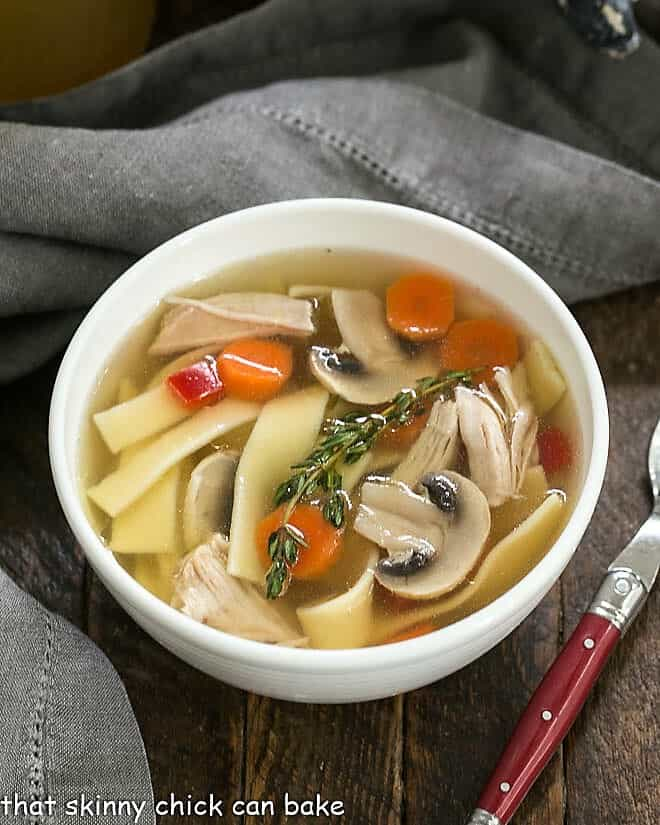 Bowl of Homemade Chicken Stock with carrots, noodles and chicken