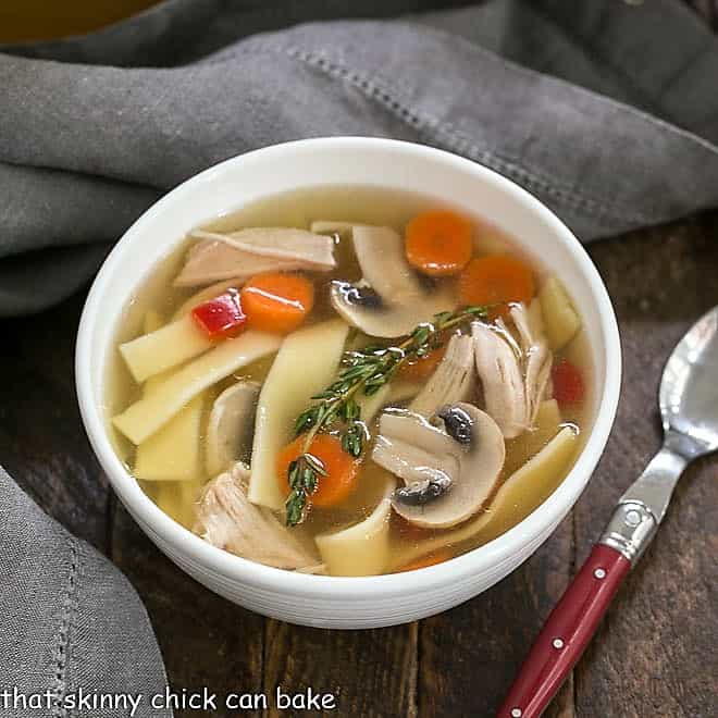 Overhead view of Homemade chicken stock, noodles and vegetables in a white bowl with a red handled spoon