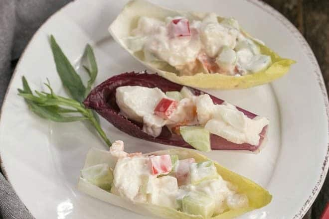Overhead view of 3 Lobster Salad in Endive Cups on a white plate