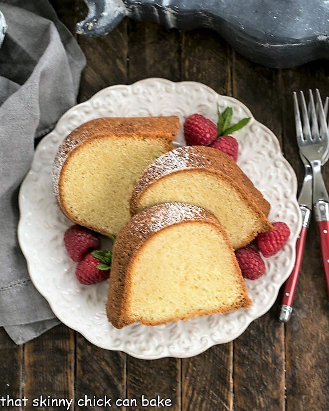 Overhead view of Sour Cream Pound Cake on a white serving plate with raspberries and mint to garnish