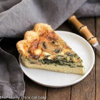 Spinach mushroom quiche slice on a round white plate