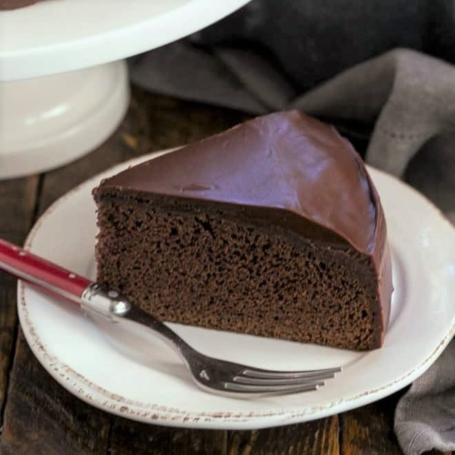 One layer fudge cake on a round white plate with a red handle fork