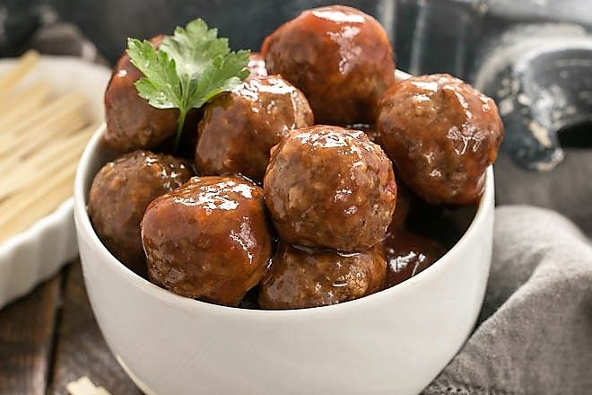Cranberry Baked Meatballs in a white bowl with toothpicks