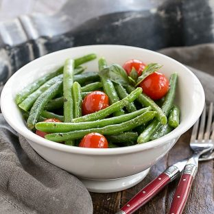 Italian Sauteed Green Beans in a white ceramic bowl with two red handled forks