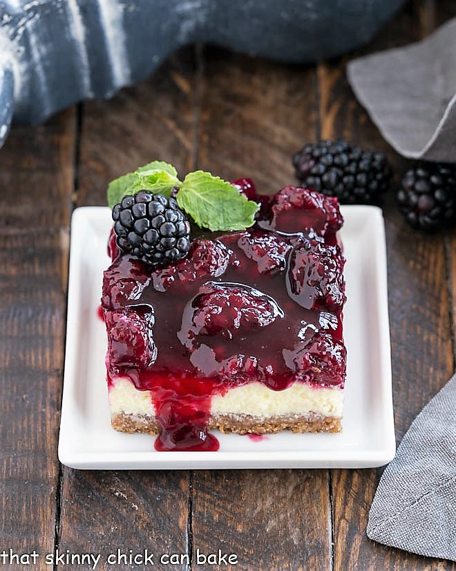 Cheesecake Bar with Berry Topping on a square white plate with a sprig of mint