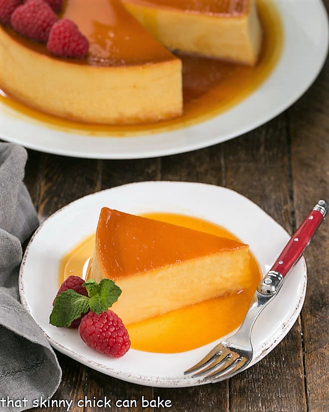 Slice of Leche Flan on a white plate with raspberry garnish