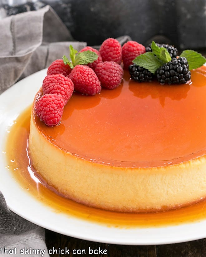 Flan Recipe topped with berries on a white plate
