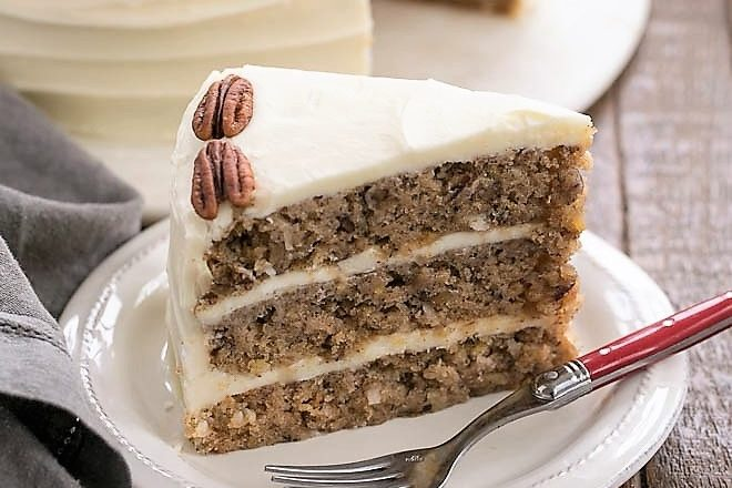 hummingbird cake slice on a white plate with a fork