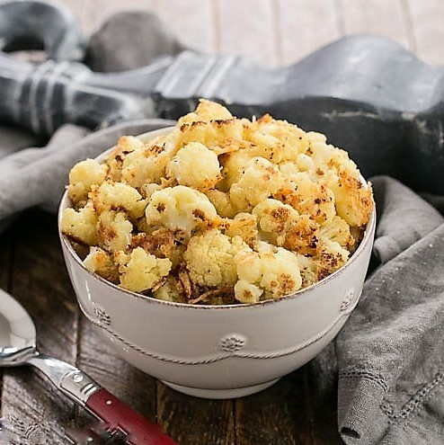 Oven Roasted Cauliflower Recipe in a white bowl with a red handle serving spoon