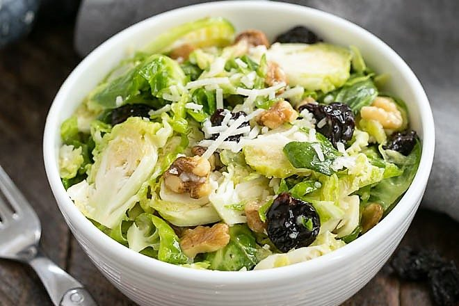 Overhead view of shaved Brussels sprouts salad with cherries in a white bowl with a red handled fork