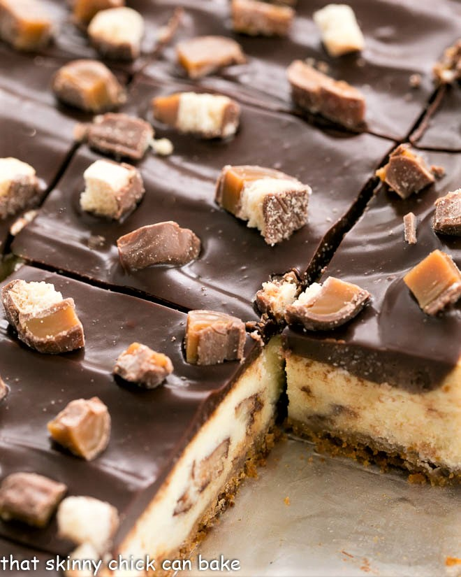 Close up of pan of sliced twix cheesecake bars