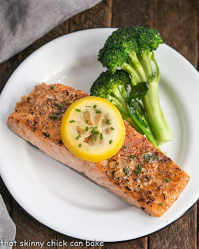 Overhead view of Salmon fillet topped with a lemon slice on a white plate with broccoli