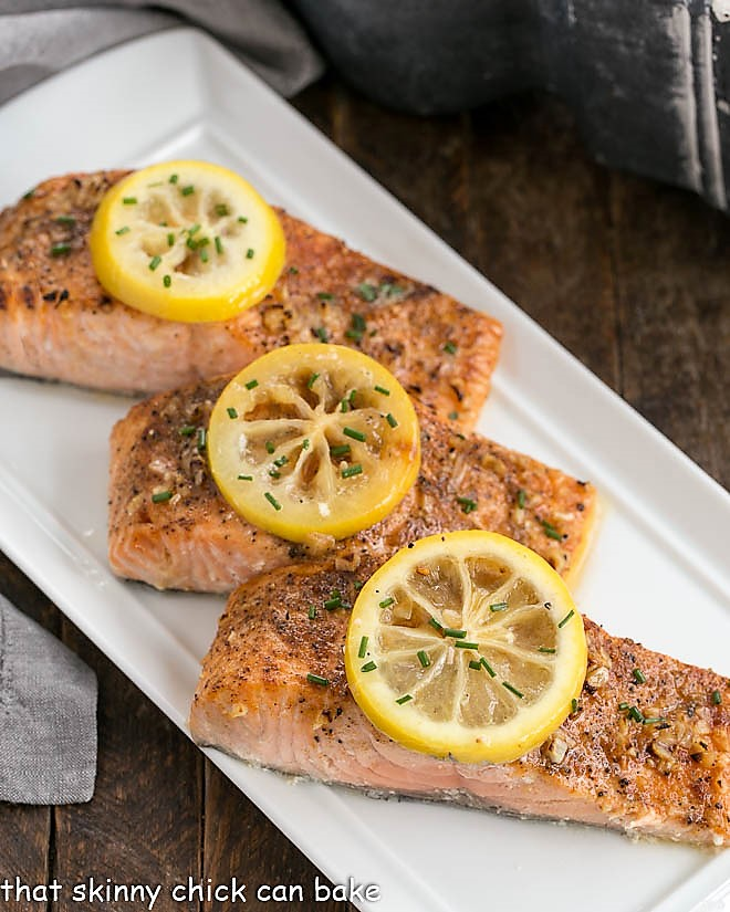 3 roasted salmon fillets topped with lemon slices on a white serving tray