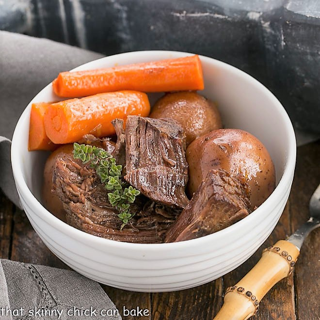 Instant Pot Beef Stew in a round white bowl with carrots and a sprig of thyme