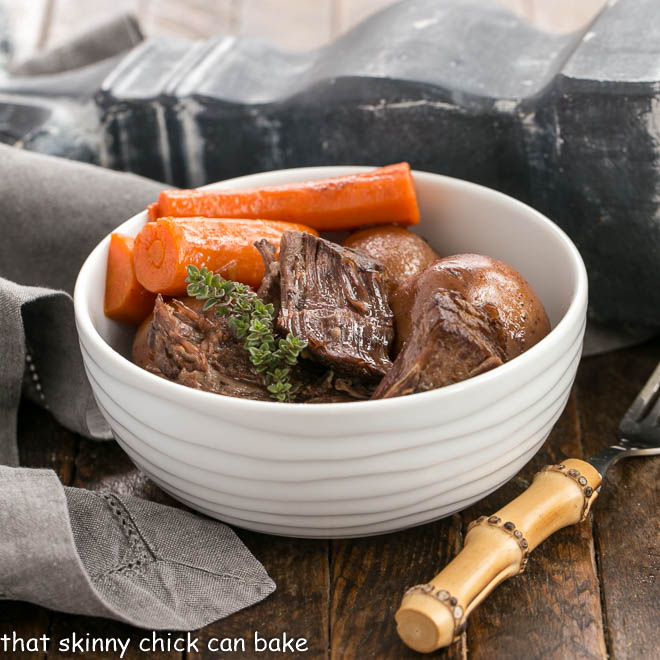 Pressure Cooker Beef stew in a white bowl with a bamboo handled fork