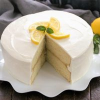 Lemon Cake with lemon curd filling on a white cake plate with a slice removed