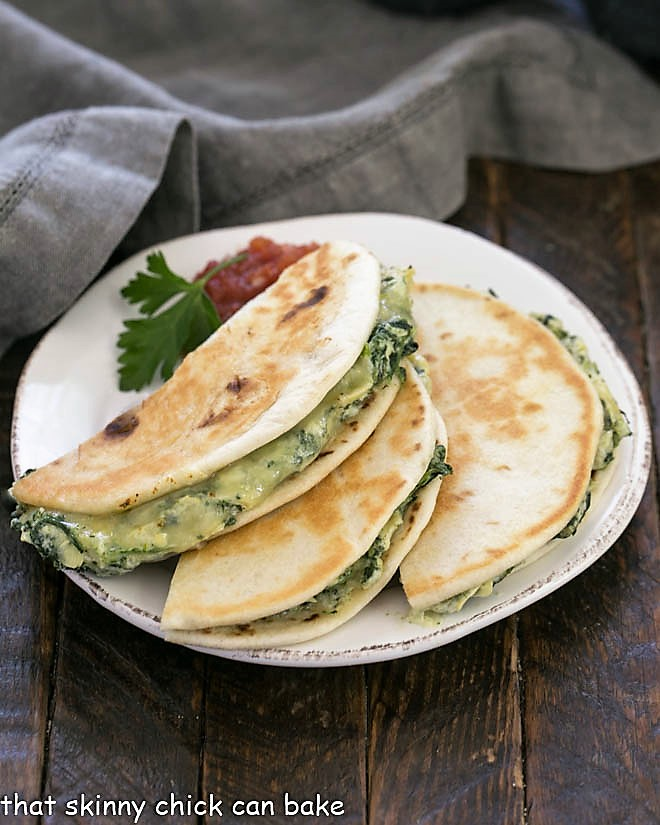 3 half quesadillas on a round white plate with a sprig of parsley and salsa