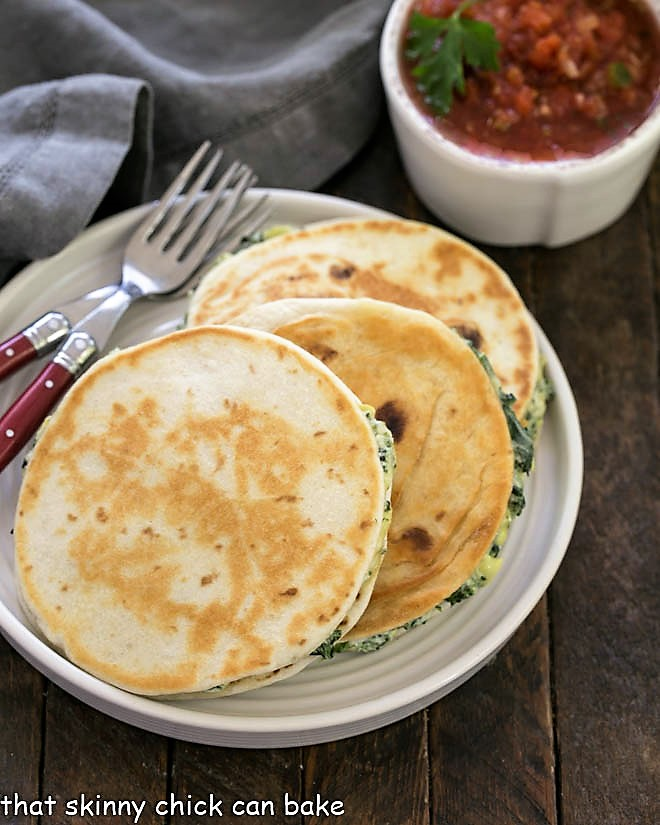 3 quesadillas on a white plate with 2 red handled forks