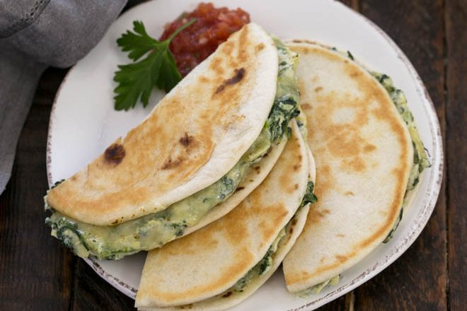 Overhead view of spinach dip quesadillas cut in half on a round white plate with salsa and a sprig of parsley