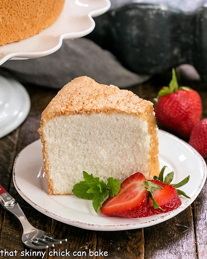 Slice of angel food cake on a white dessert plate with sliced strawberries and mink
