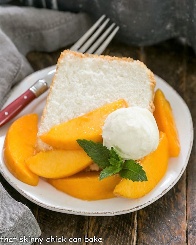 A slice of angel food cake on a dessert plate topped with fresh peach slices, whipped cream and mint