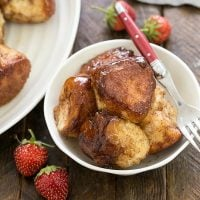 Homemade monkey bread in a small white bowl with a fork and a few small strawwberries