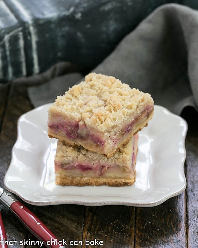 Streusel Topped Rhubarb Bars stacked on a square white plate