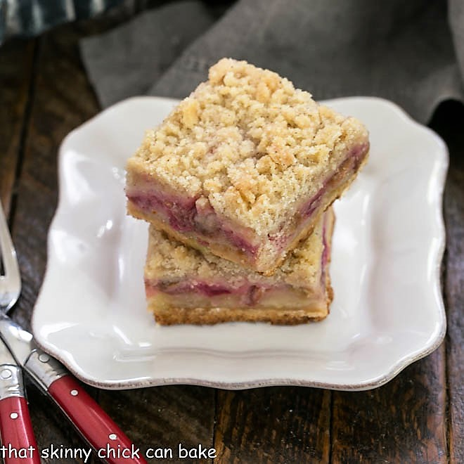 Two Two Streusel Topped Rhubarb Bars stacked on a white plate