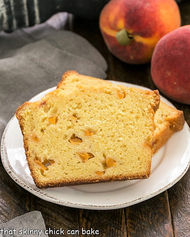 Two slices of peach cake on a white dessert plate with 2 peaches in the background