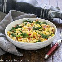 Skillet corn recipe in a white serving dish with a red handle spoon