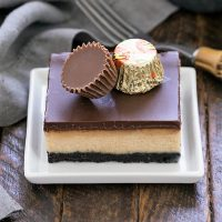 Layered peanut butter cheesecake bar topped with 2 mini peanut butter cups