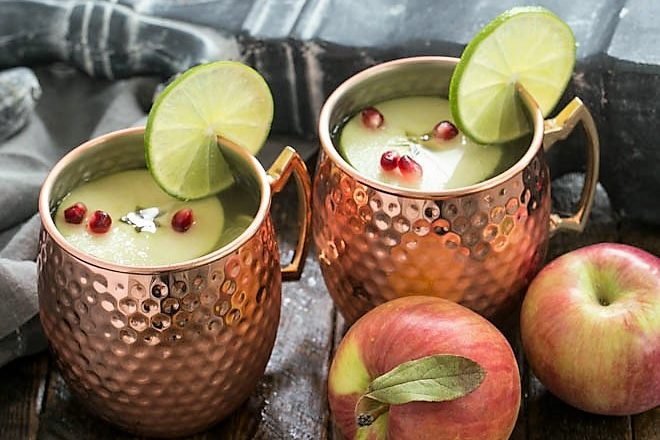 2 apple cider mules in copper mugs with 2 apples