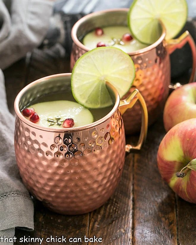Cider Mules in copper mugs with lime and apple garnishes