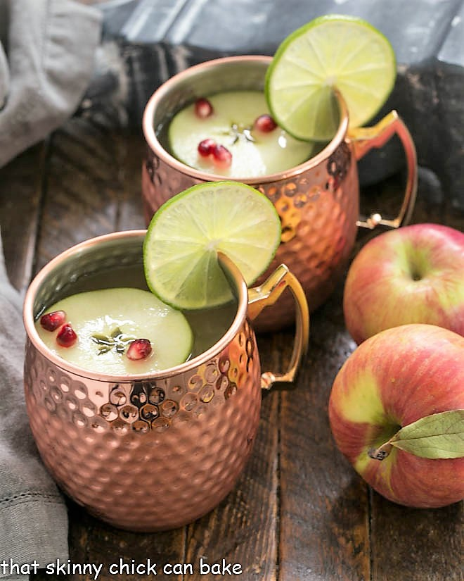 Two copper mugs filled with apple cider moscow mules