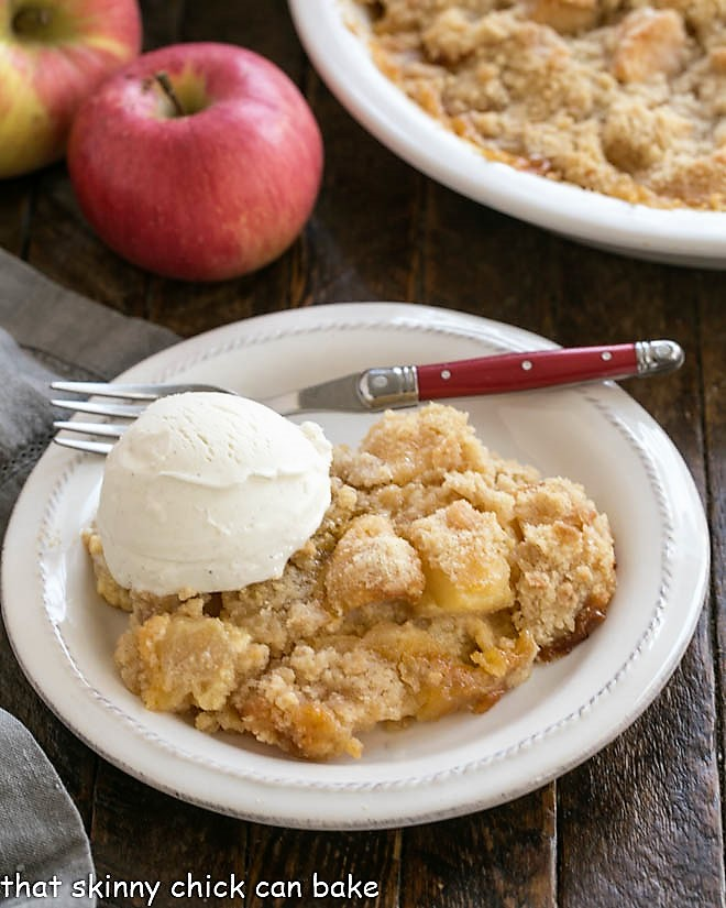 Apple crumble with a scoop of ice cream on a white dessert plate