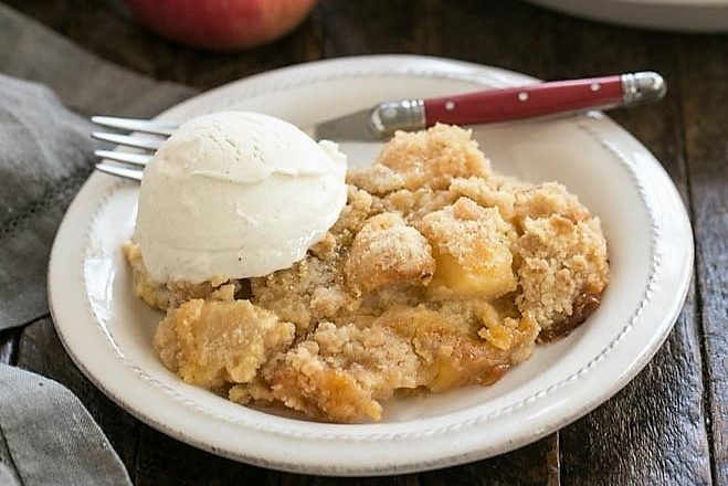 Apple Crisp with Custard on a white plate with ice creram and a red handle fork