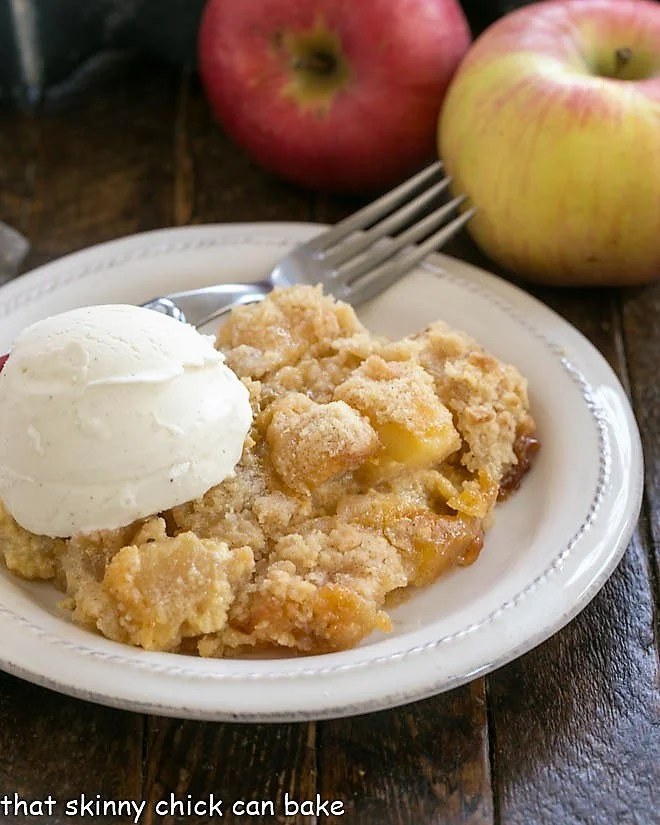 Apple crumble on a white plate with a scoop of ice cream