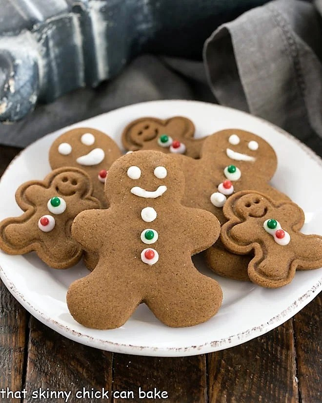 Different sized gingerbread man cookies on a round white plate